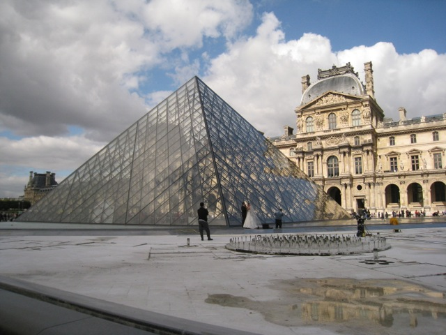 Louvre Pyramid against the classical architecture of the Louvre Museum