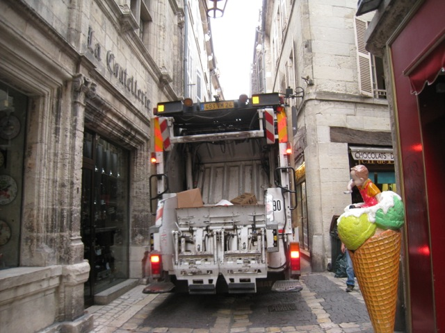 modern rubbish truck in medieval pedestrian street Perigueux